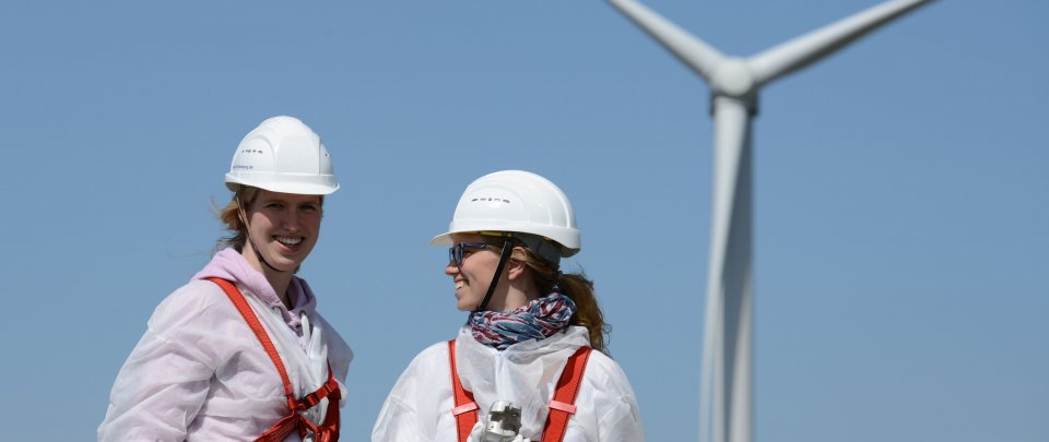 Two students in front of a wind turbine.